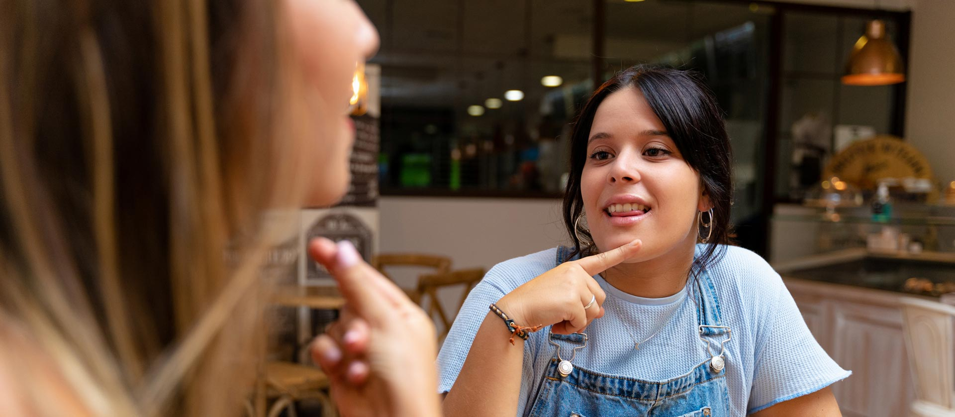 Two young women at a cafe, conversing in sign language.
