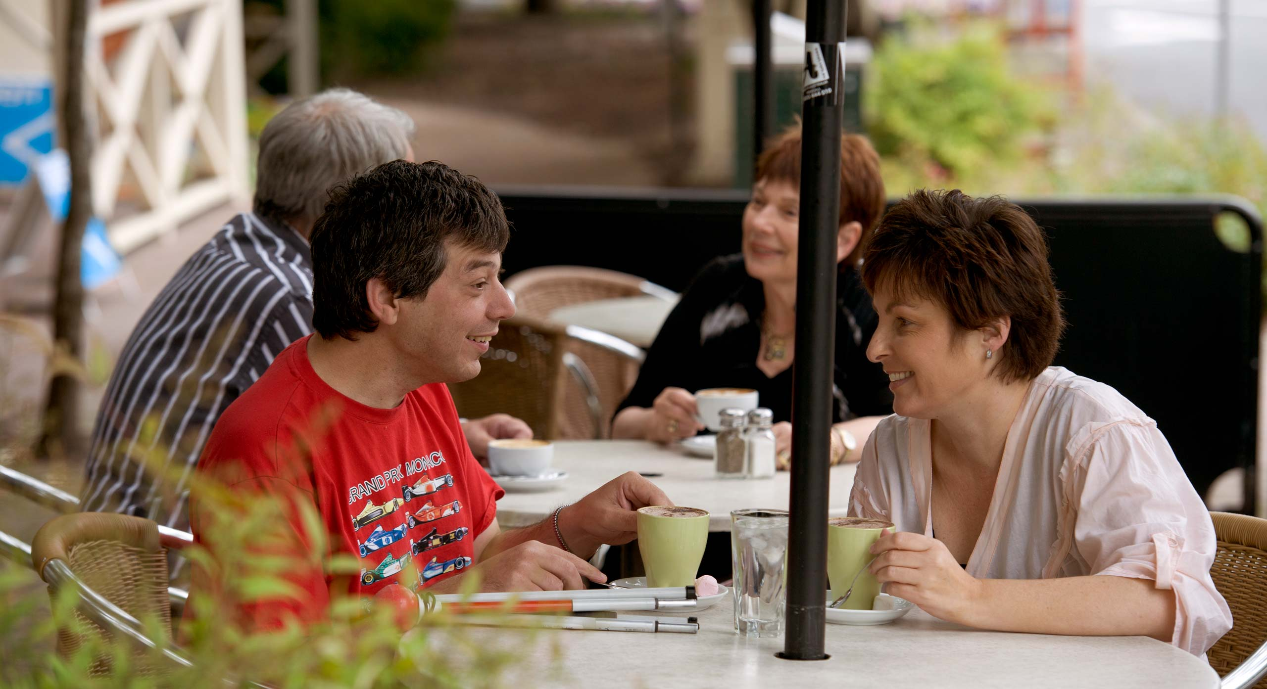 A man and woman chatting over coffee. They are both smiling.